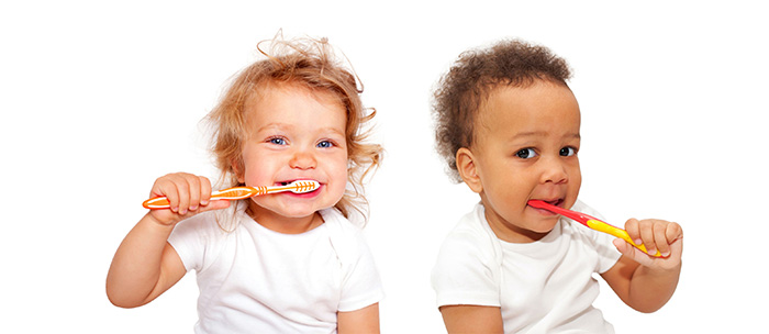 Young children brushing their teeth, featured on a page about cavity fillings in Wilson, NC.