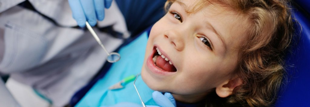 pediatric patient at a kid's dentist having his teeth examined