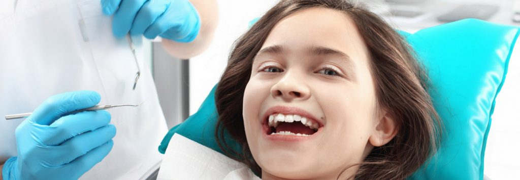 little girl at a pediatric dentist getting fluoride treatment
