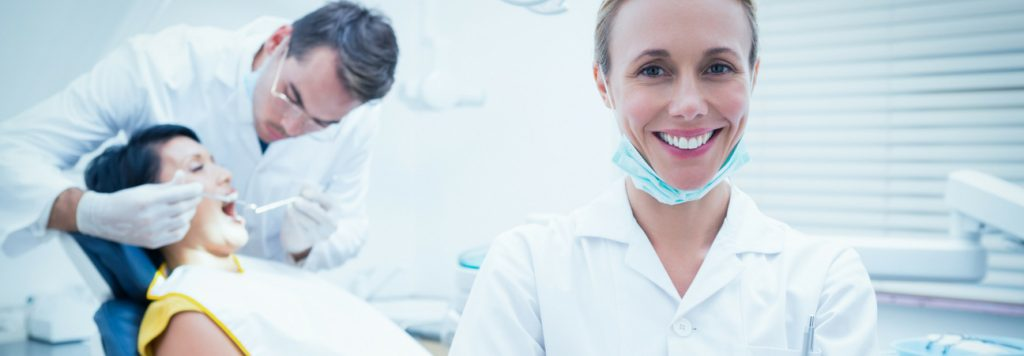 Dentist attends patient while dental assistant smiles at viewer