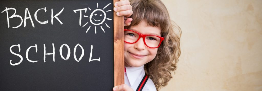 Girl in red glasses standing beside back-to-school chalkboard
