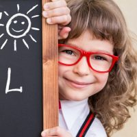 Girl in red glasses standing beside back-to-school chalkboard